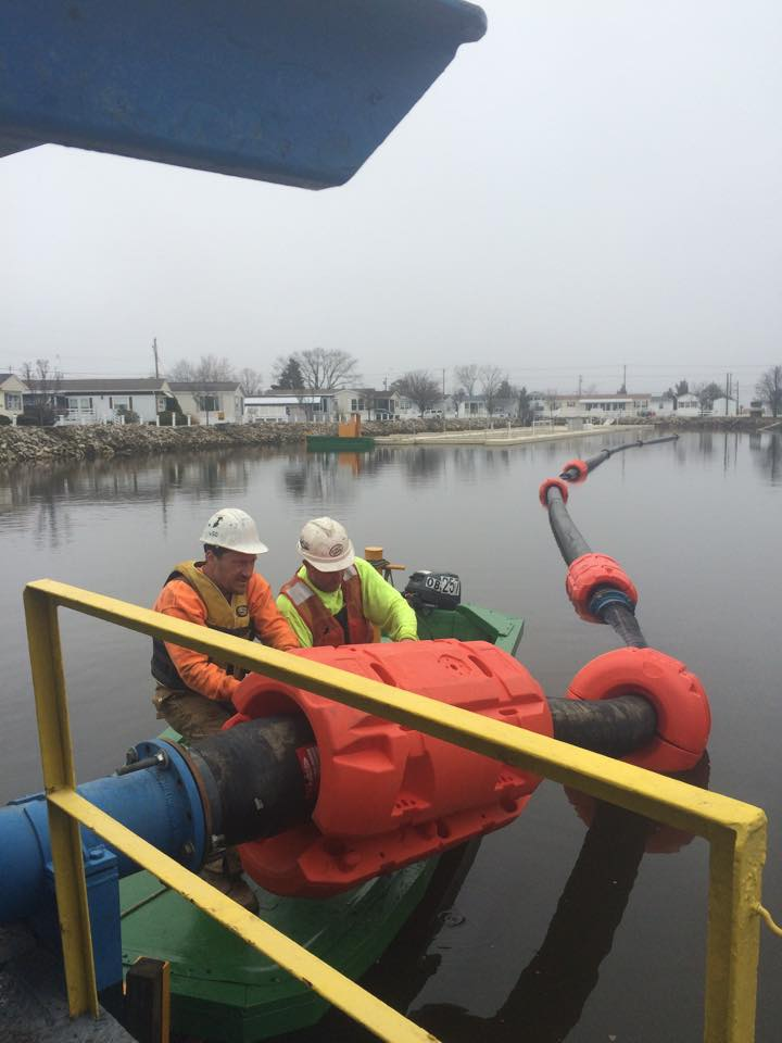 Men installing Pipe Floats (dredge floats or float collars) on pipe over water